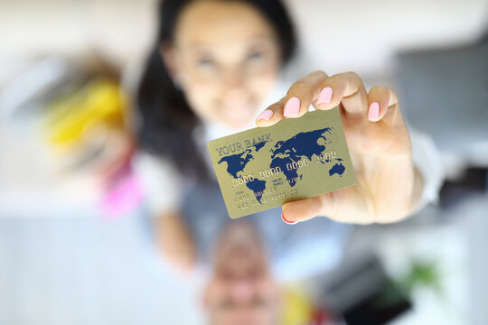 Golden currency bank card in hands of woman with man closeup. Online shopping without leaving home concept.