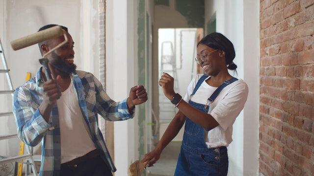 African couple dancing doing home repair and having fun