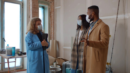 Female designer in safety mask showing house renovation process to young african couple