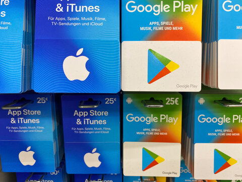 Viersen, Germany - July 9. 2020: View on apple itunes, app store and google music play gift voucher cards in shelf of german supermarket