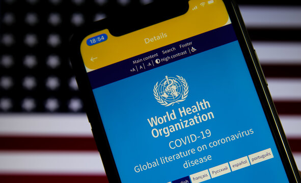 Viersen, Germany - July 8. 2020: Logo of world health organization (WHO) app on mobile phone screen. Blurred flag of USA background.