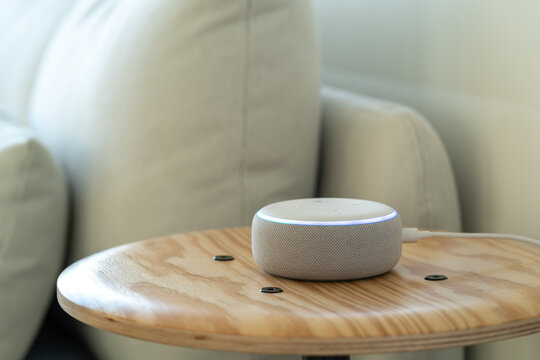 VIENNA,AUSTRIA - October 26 : A white Amazon Alexa Echo on a small wooden side table with a white sofa in the background