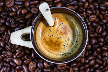 Coffee cup with roasted coffee beans on red background, coffee concept, close up coffee photo