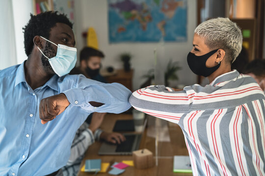 Young multiracial workers wearing face mask doing new social distance greetings bumping elbows inside co-working creative space