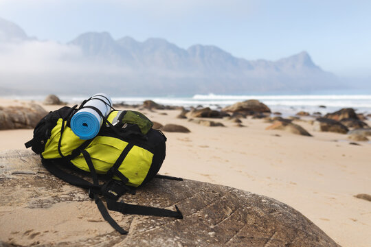Image of a backpack lying on a rock on a beach by a calm sea
