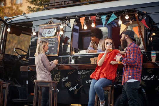 people socializing in front of truck food, drinking juices, talking