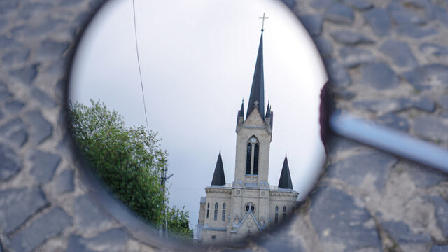 Church is reflected in the motorcycle rearview mirror. Building of architecture in the circle. Stock photos