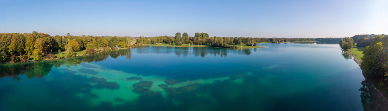 Magnificant panorama of a lake in the north of Munich with dark blue and turquise colors and trees