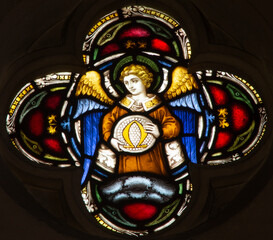 ROME, ITALY - MARCH 9. 2016: The angel with the symbolic Omega symbol on the stained glass rosette of All Saints' Anglican Church by workroom Clayton and Hall (19. cent.)