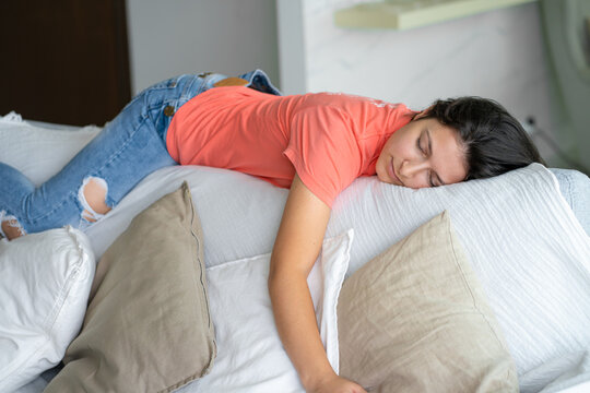 The girl fell asleep in an unusual position on the back of the sofa. Daytime sleep. Energy recovery