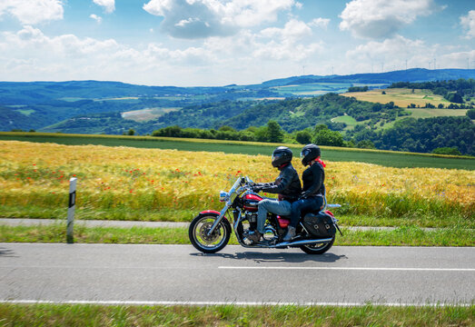 Couple on a motorcycle riding through german summer landscape