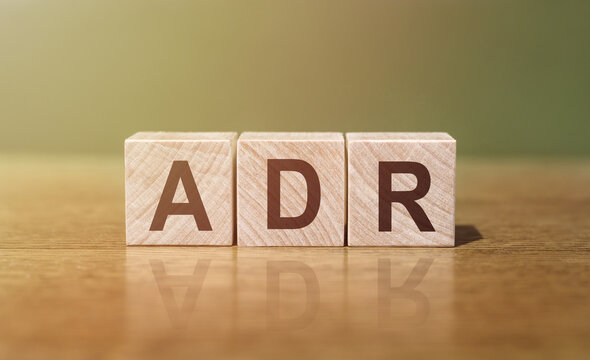 ADR (abbreviation for Adverse Drug Reaction) word written on wooden blocks on a wooden table. Medical concept.