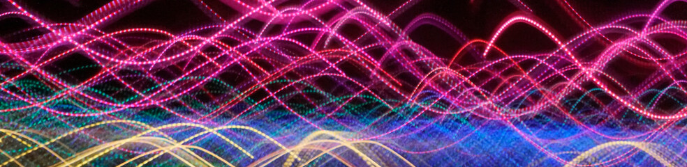 Colorful laser lights in motion flowing in a pattern. Abstract streaming light pattern.