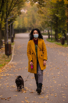 Woman with mask walking dog in park
