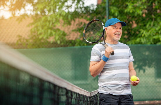 Smiling, sporting, active senior man playing tennis in the outdoor, sports pensioner, sport concept
