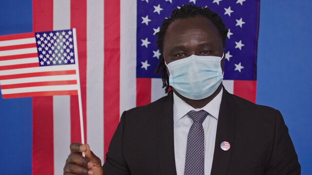 African American man with Face Mask Looking at Camera - US Flag in Background . High quality photo