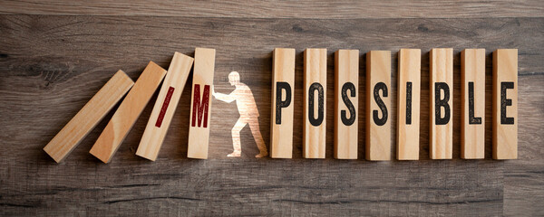 Pieces of wood with impossible and possible on wooden background