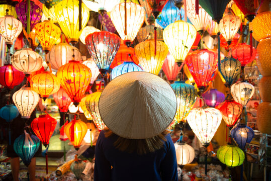 Tourist woman is wearing Non La (Vietnamese tradition hat) and looking colorful lanterns spread light on the old street of Hoi An Ancient Town - UNESCO World Heritage village.