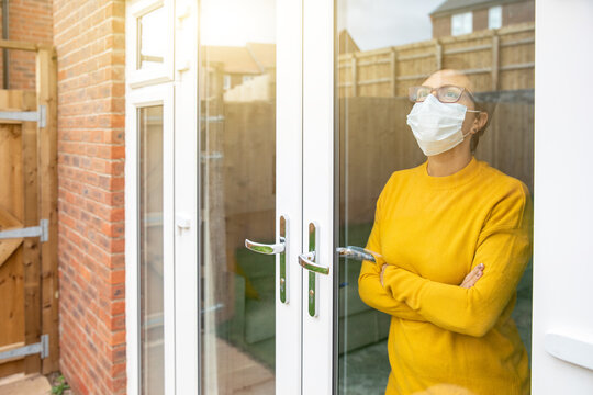 Woman wearing a face mask isolating at home and looking out of the window - Young woman feeling sad alone at home due to coronavirus quarantine and lockdown