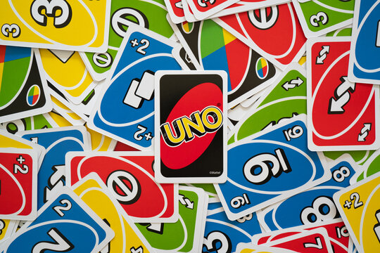 Uno game cards scattered all over the frame and one card showing the reverse side with Uno logo in the middle