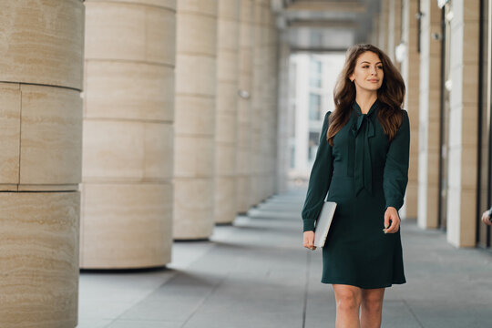 quickly goes to work late in the hands of holding a laptop with a work report. professional Manager beautiful woman brunette long hair in new dress.
