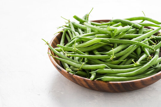 Fresh, green beans in a wooden bowl on delicate grey background. Front view