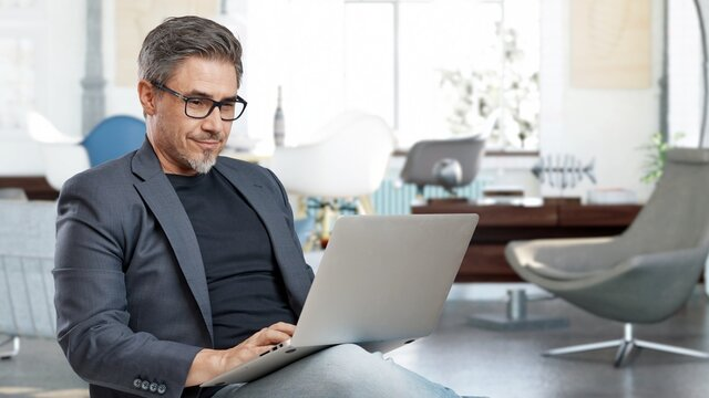 Older man sitting at home in living room working with laptop computer. Business from home in home office.
