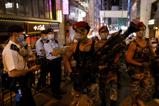 People wearing face masks and costumes walk past police officers as they celebrate Halloween at Lan Kwai Fong in Hong Kong