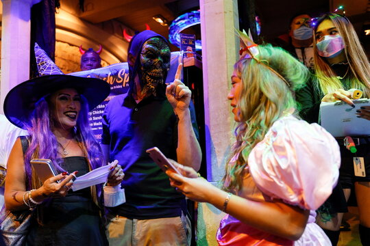 People wear face masks and costumes celebrating Halloween at Lan Kwai Fong, a popular nightlife destination in Central, following the coronavirus disease (COVID-19) outbreak, in Hong Kong