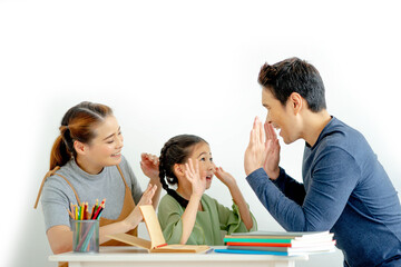 Asian young mother and father with little daughter sit at desk learning and making homework...