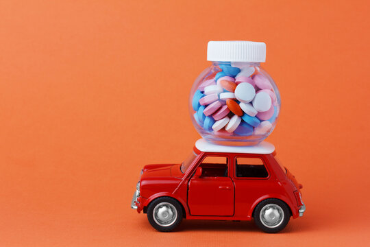 red toy car delivering a bottle of pills.  Internet pharmacy, online order.