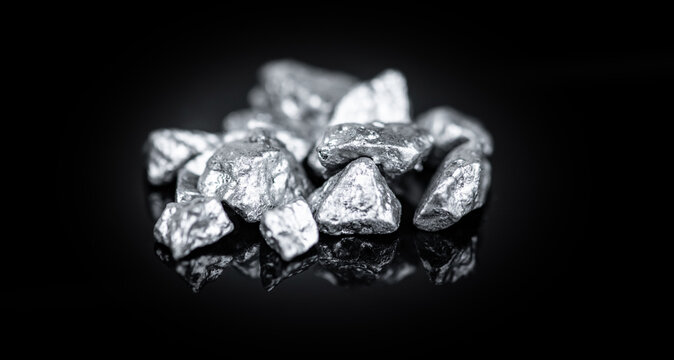 Heap of silver nuggets isolated on black background