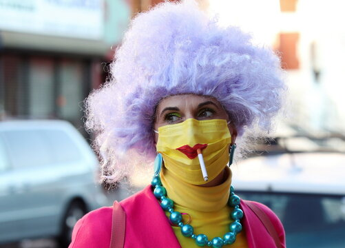 A woman dressed up for Halloween as a Simpsons character smokes a cigarette through a protective mask in Brooklyn
