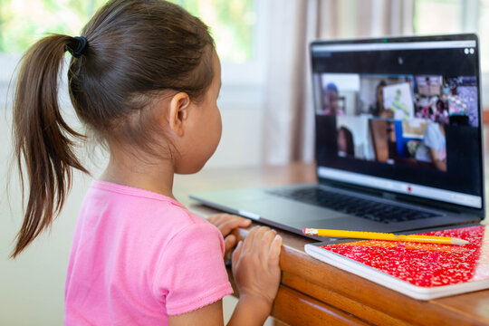 A little kid learning online at home school, video class call, book and pencil.