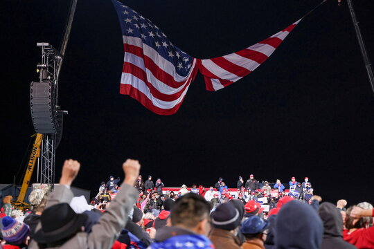 The wind spins a large U.S. flag into two halves as U.S. President Trump rallies with supporters at a campaign event in Montoursville, Pennsylvania