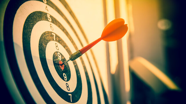 Bulls eye or dart board has red dart arrow throw hitting the center of a shooting target for business targeting and winning goals business concepts.
