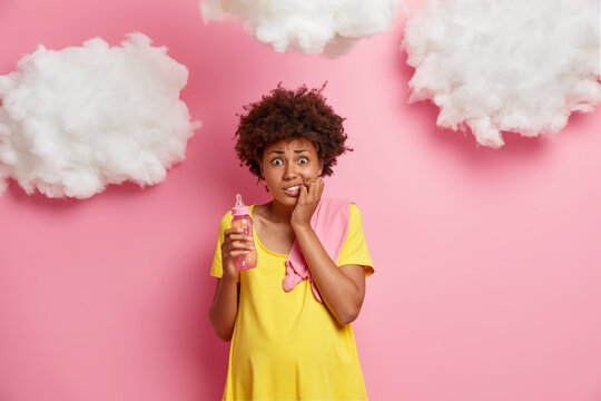 Photo of worried nervous pregnant ethnic woman bites finger nails and looks anxiously at camera holds milk bottle poses with baby stuff against rosy background has big stomach. Maternity concept