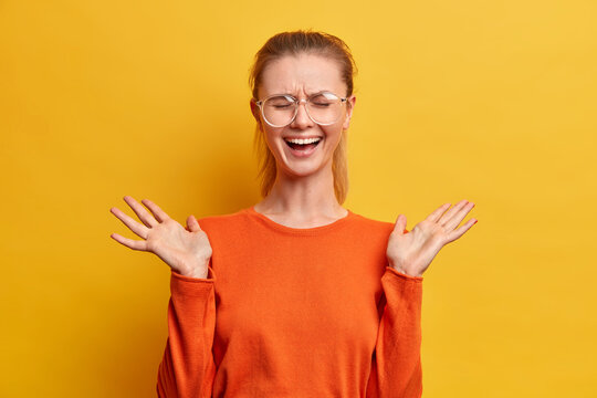 Overjoyed young nerdy female model laughs hysterically raises palms closes eyes shows white teeth wears big optical glasses and orange sweater isolated over yellow background. Emotions concept