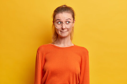 Half length shot of pretty millennial girl presses lips and looks away reacts on something with bewilderment wears big spectacles orange jumper isolated over yellow background. Human reaction