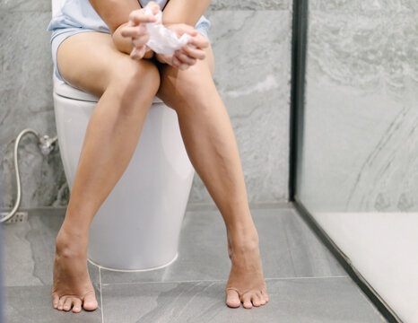 Closeup woman sitting on toilet in the morning with depressed feeling, selective focus