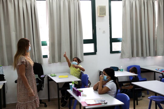 Pupils and a teacher wear protective face masks in a classroom as Israel reopens first to fourth grades, continuing to ease a second nationwide coronavirus disease (COVID-19) lockdown, at a school in Rehovot