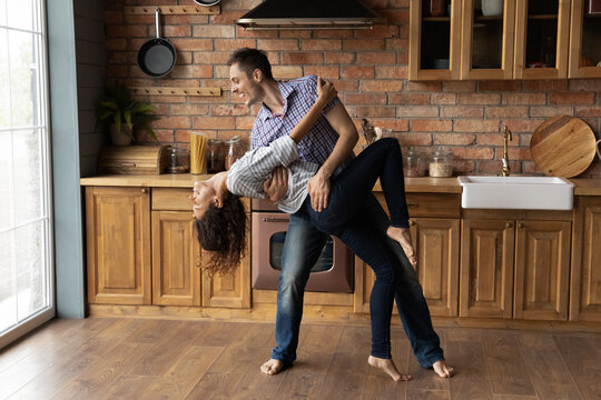 Overjoyed Caucasian man and woman enjoy happy leisure weekend in new home dancing waltzing together. Smiling young couple renters or tenants have fun on cozy renovated modern kitchen. Realty concept.
