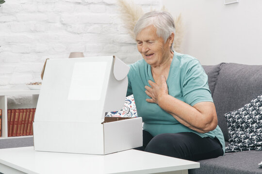 Senior woman opening parcel box at home. Happy smiling elderlyr woman looking into open parcel box at home.