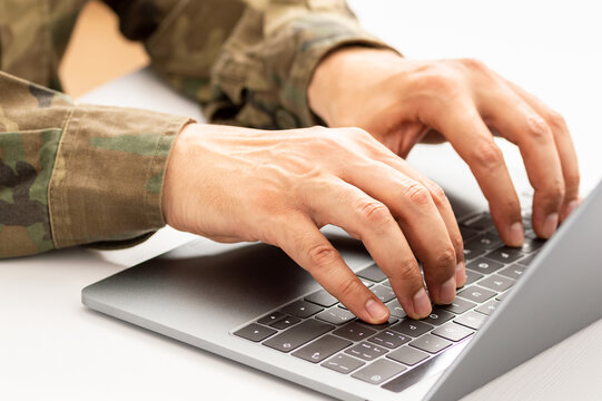 Closeup shot of a unrecognizable military person typing on a laptop keyboard