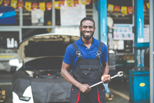 Portrait of attractive African man smiling to the camera and big wrench tools in hand. Expertise mechanic working in automobile repair garage.