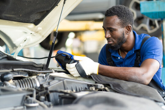 Professional car mechanic repair service and checking car engine by Diagnostics Software computer. Expertise mechanic working in automobile repair garage.