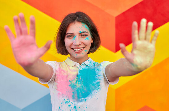 Happy woman with colorful face and clothes showing hands