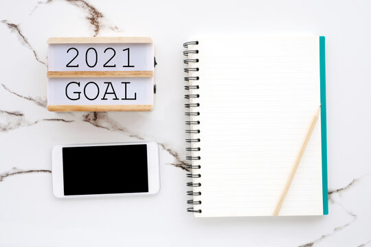 2021 goal on wood box, blank notebook paper, smart phone with blank screen on white marble background, 2021 new year goal mock up, template, flat lay