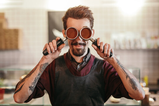 Hipster barista with portafilters in coffee shop