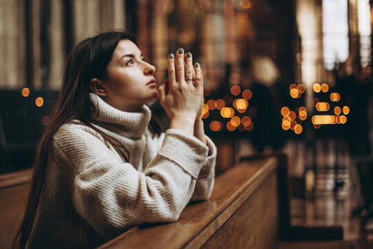 a young pretty woman came to the temple to pray to God. The parishioner of the church sits on a bench with her hands folded for prayer and heartily prays. copy space